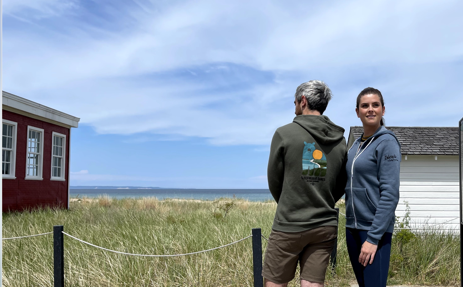 unisex fit zip up hoodie in military green with Sleeping Bear Dunes 50th Bear Logo on the back. Blue zip hoodie showing Friends Logo on the Front.